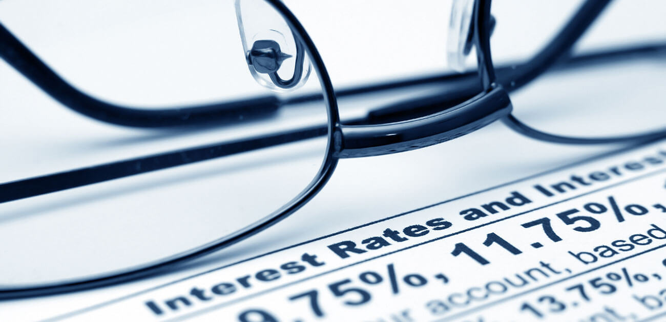 glasses on document with interest rates and repricing information image